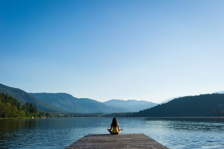 Female meditating doing sukhasana or Easy Pose during a yoga working at a pristine mountain lake stockstudioX via Getty Images