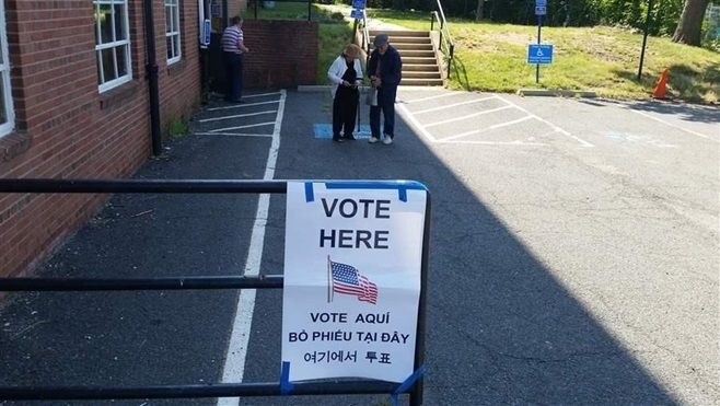 """A """"vote here"""" sign translated into Korean, Spanish and Vietnamese hangs near the entrance to a polling place set up in the Wi"""