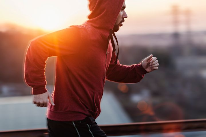 A picture of a man running and exercising beneath a clear sky, along a steal fence. He is wearing a red sweater with his hoodie pulled up and black shorts. In the distance below is some buildings and the sun is setting giving a nice warm light. Geber86 via Getty Images