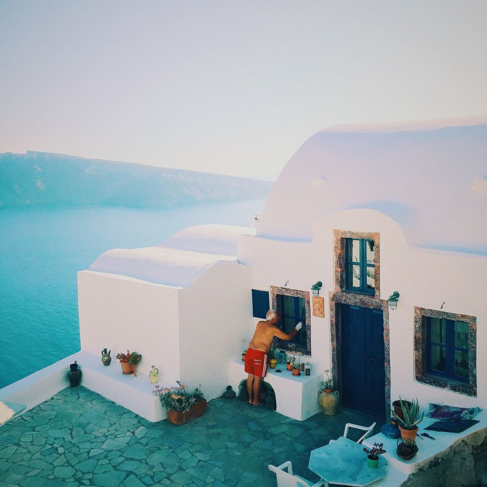 """YuMing Guan. Guangdong, China.<strong>2ndPlace –Lifestyle.<br /><br /><i><br /></i></strong><i>""""This picture was taken in the summer of 2015, in Oia, a beautiful small town of Santorini. Tourists from around the globe gathered at the cliff to see the breathtaking sunset that is known as one of the Greatest Views in the World. Everyone was amazed by the stunning moment with awe and applauds, that's when this local old man caught my attention. He was so concentrated and undisturbed, as if no crowd or view deserves his attention better than his own windowsill. I guess perhaps in his mind, the Greatest View in the World is HOME.""""</i><strong><br /></strong>"""