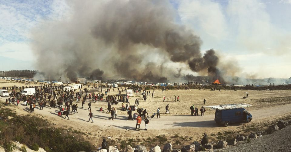 """Samuel Nacar. Albacete, Spain.<strong>1st Place –News/Events.</strong><br /><br />The nomads of Europe<br />""""Monday 24th of October started the eviction of the biggest migrant camp in Europe named The Jungle, located in northern France only 5 kilometers away from the city of Calais. On Wednesday 26th of October the camp was set on fire and thousands of migrants had to leave, some of them were relocated while others were not. In this photograph you can see thousands of migrants being evicted from the camp due to the many fires.""""<strong><br /></strong>"""