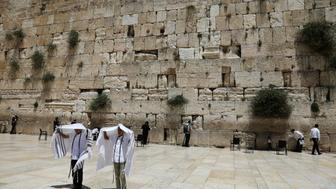 Youth hold their prayer shawls as they stand in front of the Western Wall, Judaism's holiest prayers site in Jerusalem's Old City May 17, 2017. REUTERS/Ronen Zvulun