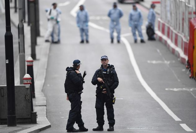 Armed police officers patrol London Bridge the day after the