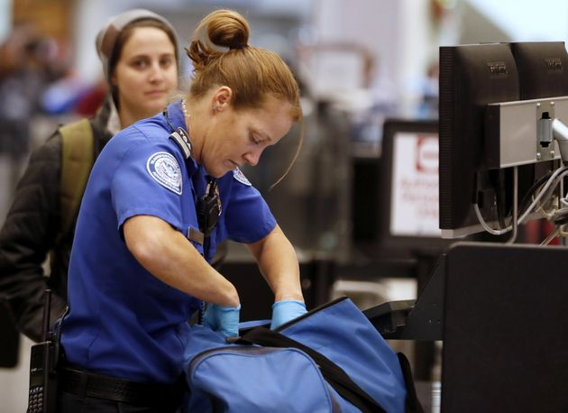 A TSA officer checks a traveler's bag at a screening location at Salt Lake City International Airport...