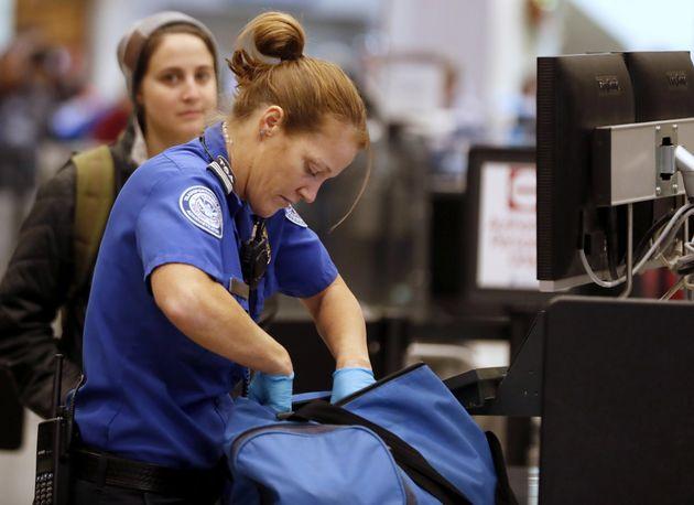 A TSA officer checks a traveler's bag at a screening location at Salt Lake City International Airport in Utah.