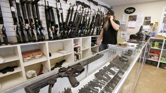 "An AR-15 sits on a display case as Willy Ludlow, owner of  the ""Ready Gunner"" gun store, talks on the phone in Provo, Utah, U.S., June 21, 2016. REUTERS/George Frey"