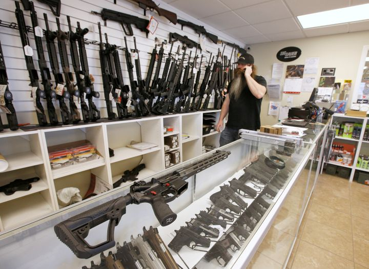 "An AR-15 sits on a display case as Willy Ludlow, owner of the ""Ready Gunner"" gun store, talks on the phone in Provo, Utah, U."