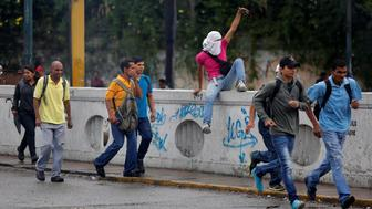 People move to cover as demonstrators rally against Venezuela's President Nicolas Maduro's government in Caracas, Venezuela, June 28, 2017. REUTERS/Ivan Alvarado