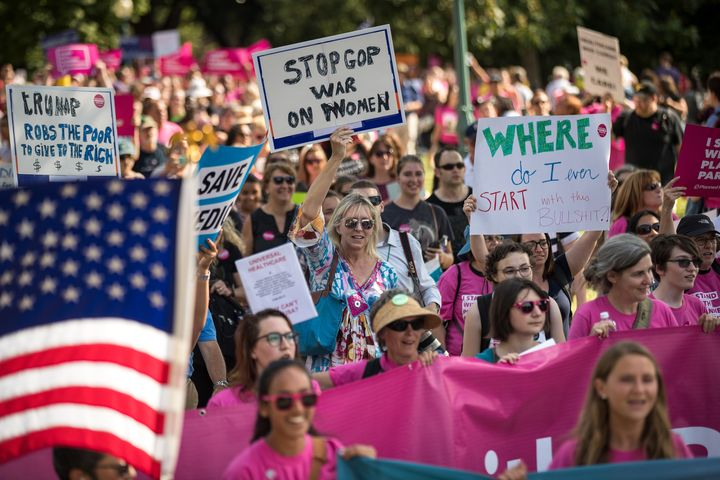Activists march around the U.S. Capitol to protest the Senate GOP health care bill, onWednesday.