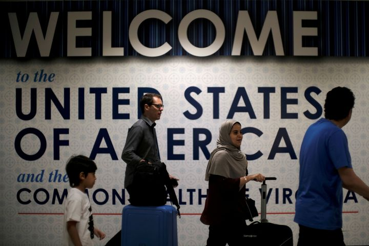 International passengers arrive at Washington Dulles International Airport on Monday, after the U.S. Supreme Court granted pa
