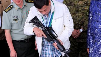 "Philippine President Rodrigo Duterte inspects an automatic rifle during the turnover ceremony of China's urgent military assistance, given ""gratis"" to the Philippines at Clark Air Base, near Angeles City, Philippines June 28, 2017. REUTERS/Romeo Ranoco"
