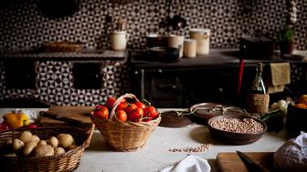 Tomatoes, potatoes, and beans in baskets on a table in a rustic kitchen.