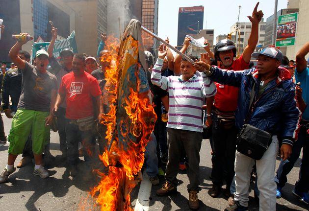 Simpatizantes del expresidente Hugo Chávez queman una bandera con el símbolo de un líder de la oposición...