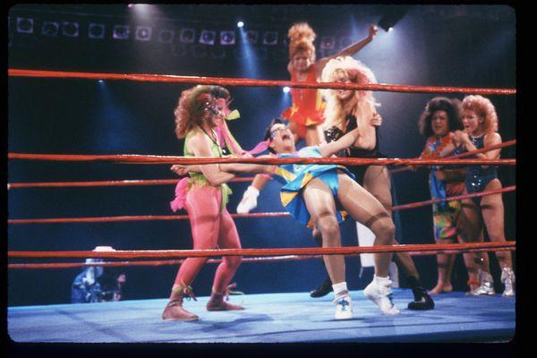 GLOW Girls wrestle in the ring.