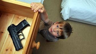 Boy (4-6 years old) reaching up to a bedroom drawer that contains a gun