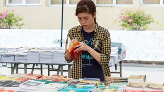 Hanoi, Vietnam - Sep 29, 2015: Young female student with choose the book on the street market in Hanoi, Vietnam
