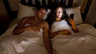 Young couple. Wife on phone while husband is sleeping.