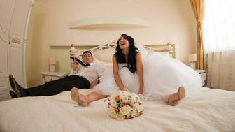 young beautiful bride and groom on a hotel bed