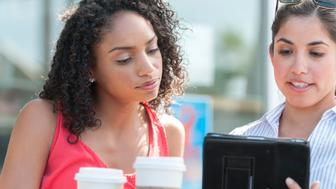 Two attractive ethnic women with disposable coffee cups look at a computer tablet at an outdoor coffee shop patio in Los Angeles, California, USA.  African American and Hispanic ethnicity.