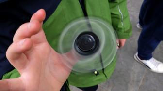 Eight-year-old Tom Wuestenberg plays with a fidget spinner in a park in New York on May 23, 2017.  It was supposed to calm nerves, relieve stress and improve concentration but the new-anti fidget toy spreading fast through US and European schools is whipping up anger among teachers on both sides of the Atlantic. Just months after the 'fidget spinner' first whirled its way into the hands of antsy youngsters, some schools have already banned it -- sparking a debate about difficulties children experience concentrating.  / AFP PHOTO / JEWEL SAMAD        (Photo credit should read JEWEL SAMAD/AFP/Getty Images)