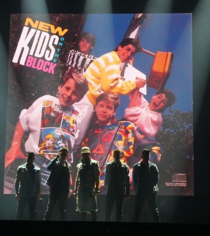 The New Kids stand next to the album cover of their 1986 debut album