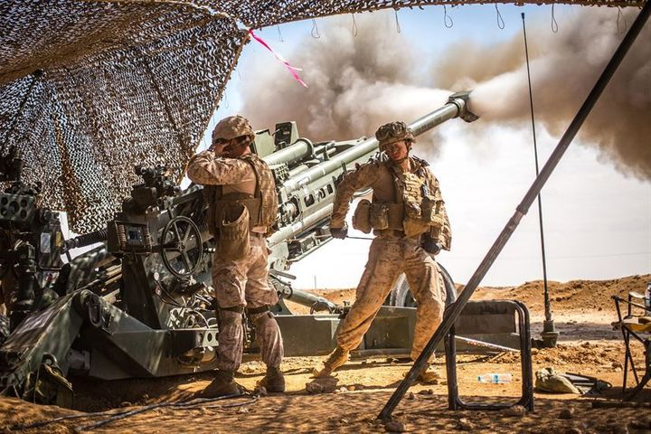 Marines with the 11th Marine Expeditionary Unit fire an M777 Howitzer during a fire mission in northern Syria as part of Oper