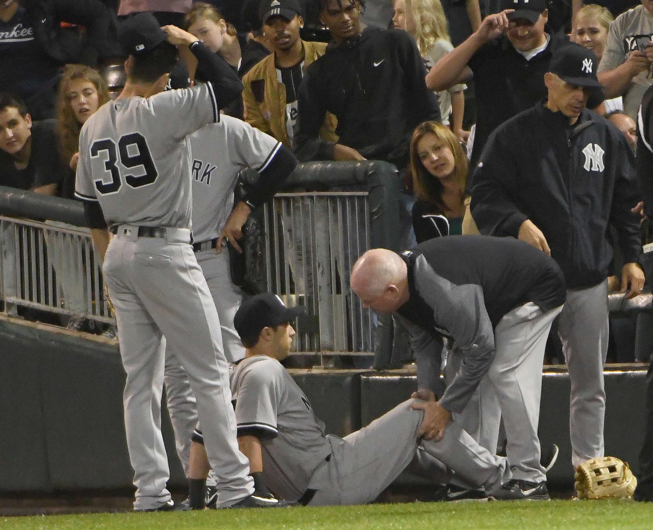 CHICAGO, IL - JUNE 29: Dustin Fowler (on the ground) of the New York Yankees sits on the ground as the trainer looks at his leg after trying to catch a foul ball hit by Jose Abreu (not Pictured) of the Chicago White Sox. Fowler had to leave the game and was taken off the field on a cart, on June 29, 2017 at Guaranteed Rate Field  in Chicago, Illinois. (Photo by David Banks/Getty Images)