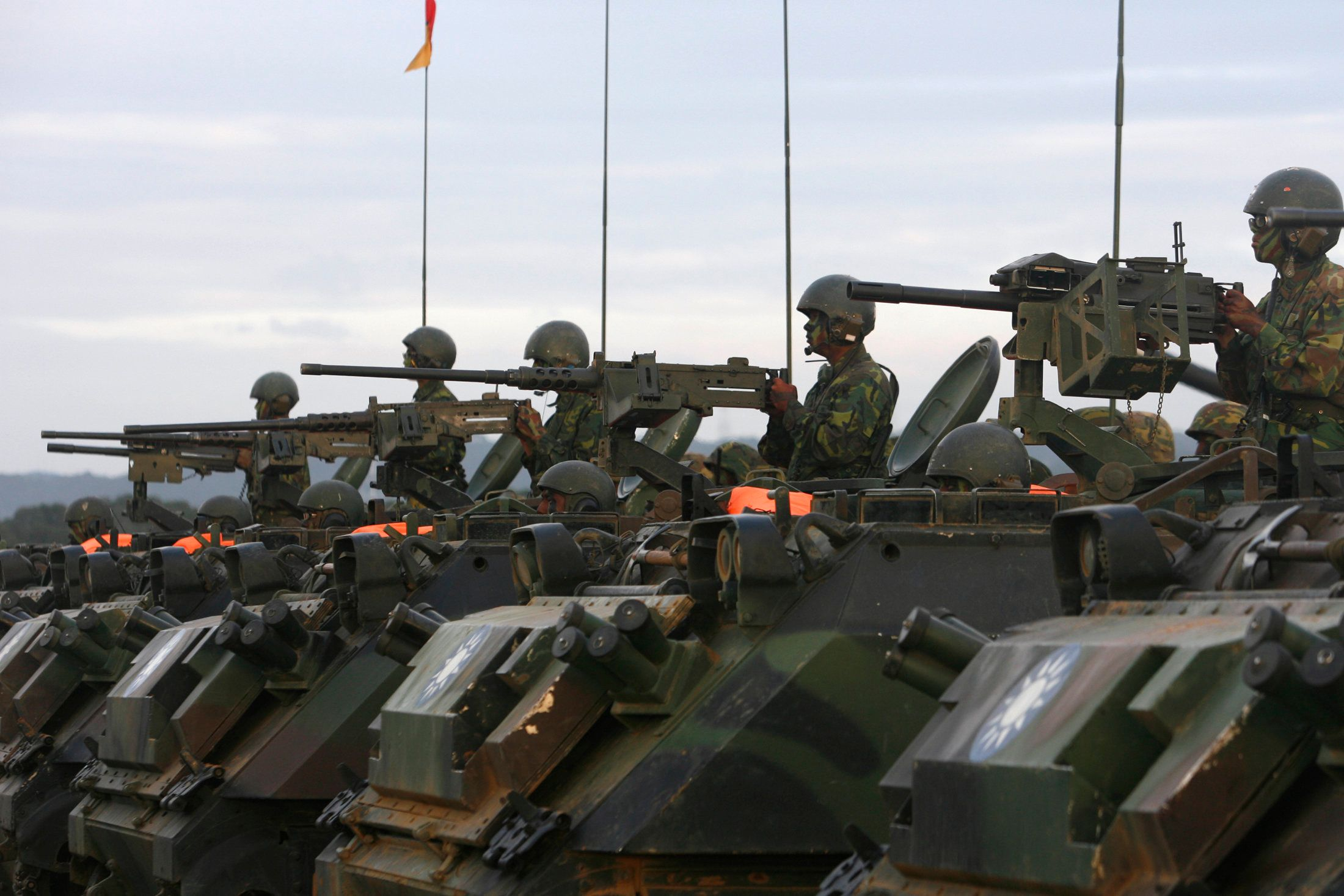 Soldier aim their weapons on CM21A1 armoured infantry fighting vehicles during an army exercise in Hsinchu, central Taiwan January 27, 2010. A U.S. arms sale to Taiwan is likely to offer a short-term boost to the flagging popularity of the island's president by making him look strong in standing up to China, but may delay the critical trade deals he has pushed.    REUTERS/Nicky Loh (TAIWAN - Tags: MILITARY POLITICS)