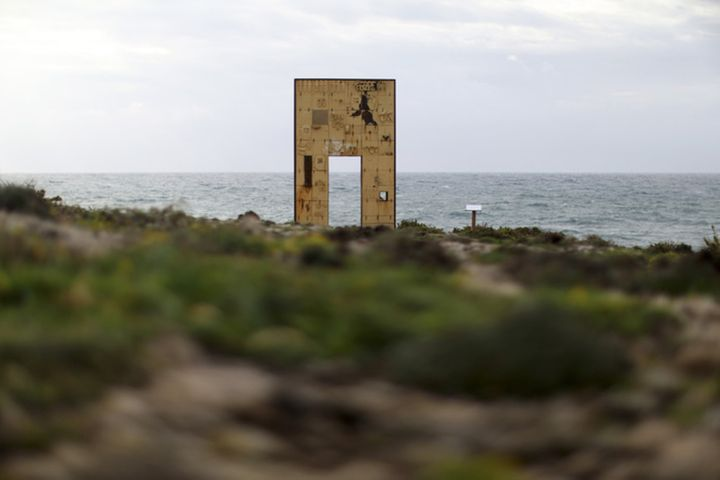 """The """"Door of Europe"""" monument, which commemorates migrants who died on their journey, is seen on the southern Italian island"""
