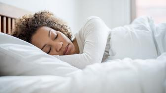 Tired black woman sleeping and looking very comfortable in her bed