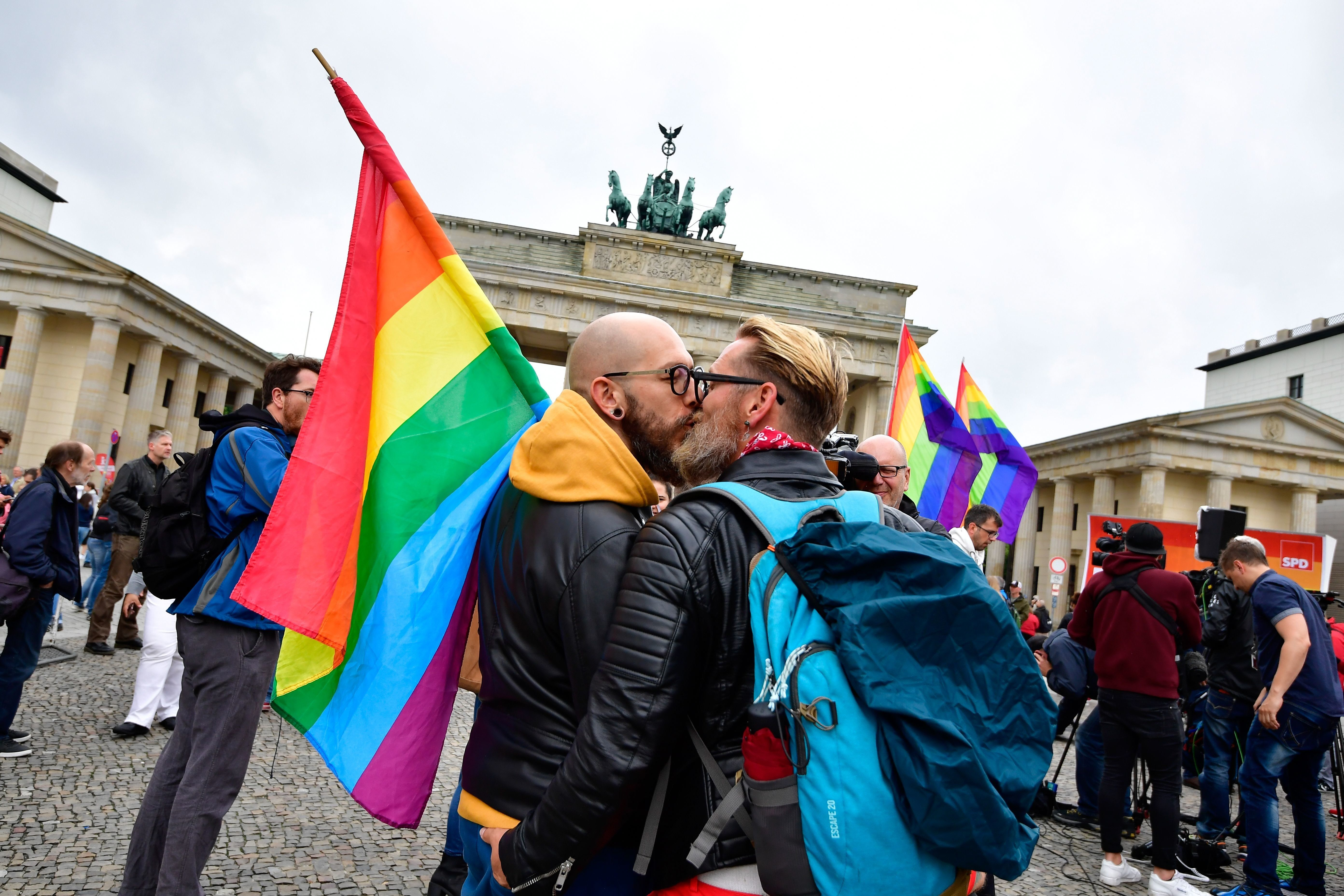 Two men kiss as they attend a rally of gays and lesbians in front of the Brandenburg Gate in Berlin on June 30, 2017. The German parliament legalised same-sex marriage, days after Chancellor Angela Merkel said she would allow her conservative lawmakers to follow their conscience in the vote. / AFP PHOTO / Tobias SCHWARZ        (Photo credit should read TOBIAS SCHWARZ/AFP/Getty Images)
