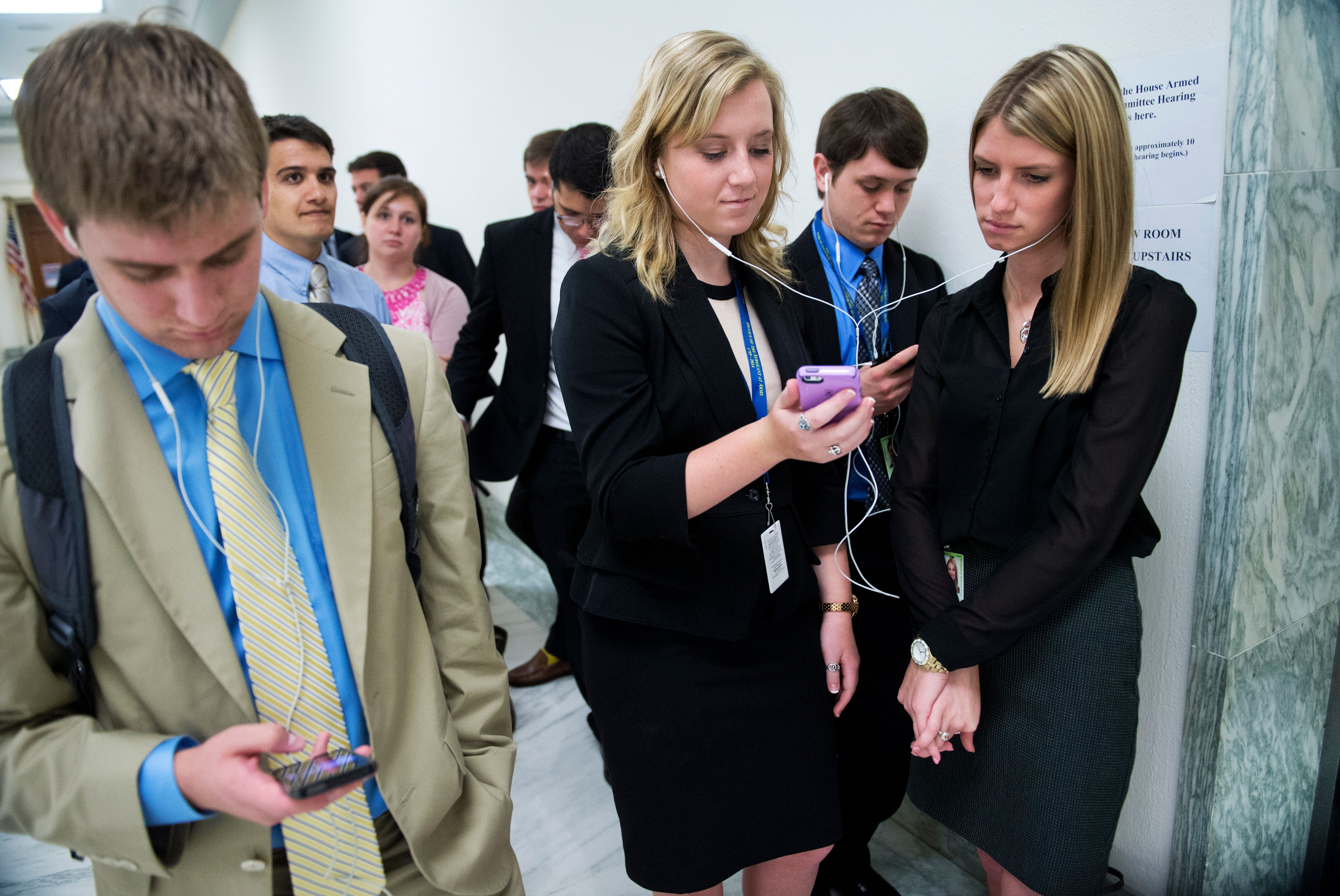 UNITED STATES - JUNE 11: Jennifer Stubbs, center, and Megan Foreman, interns for Rep. Ralph Hall, R-Texas, wait in line to see Secretary of Defense Chuck Hagel testify before a House Armed Services Committee hearing in Rayburn Building on the Sgt. Bowe Bergdahl prisoner exchange, June 11, 2014. (Photo By Tom Williams/CQ Roll Call)