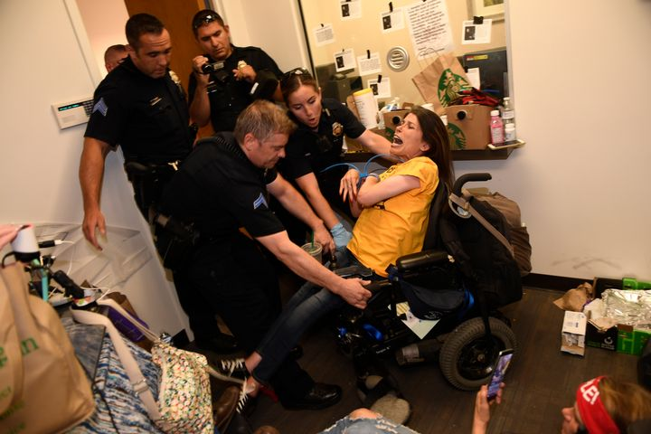 Denver police arrest Dawn Russell for refusing to leave the offices of Sen. Cory Gardner (R-Colo.) on June 29.