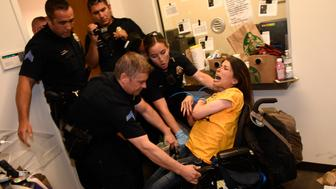 DENVER CO - JUNE 29: Dawn Russell gets arrested by Denver police officers after refusing the vacate the offices of Senator Cory Gardner on June 29, 2017 in Denver, Colorado. A handful of people, all of whom are with ADAPT, held a sit-in for 58 hours in the tiny front lobby space in the office of Colorado Senator Cory Gardner. They are asking the senator to vote against the new health care bill. As they were arrested protesters chanted 'I would rather go to jail than die without Medicaid.' ADAPT is a national grass-roots community that organizes disability rights activists to engage in nonviolent direct action, including civil disobedience, to assure the civil and human rights of people with disabilities to live in freedom.  (Photo by Helen H. Richardson/The Denver Post via Getty Images)