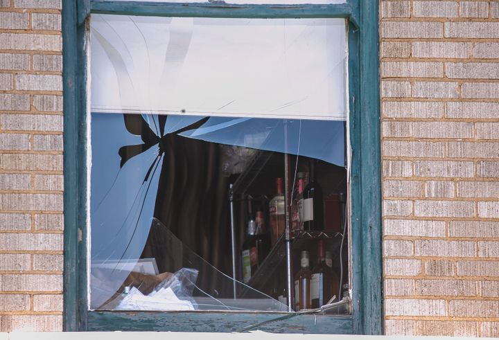 A broken window at the Ultra Power Lounge as law enforcement collects evidence on a shooting that authorities believe stemmed from a dispute during a concert.