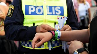 A police officer attaches a bracelet to a visitor's wrist, as part of the Swedish police summer campaign to make the problem of sexual harassment among young people visible, at Bravalla Festival in Norrkoping, Sweden July 1, 2016. Five rapes and a number of sexual assaults were reported at the popular Bravalla Festival over the weekend. TT News Agency/Izabelle Nordfjell/via REUTERS ATTENTION EDITORS - THIS IMAGE WAS PROVIDED BY A THIRD PARTY. FOR EDITORIAL USE ONLY. SWEDEN OUT. NO COMMERCIAL OR EDITORIAL SALES IN SWEDEN. NO COMMERCIAL SALES.