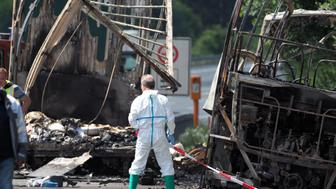 A forensic expert works at the scene where a tour bus burst into flames following a collision with a trailer truck on the highway A9 near Münchberg, southern Germany, on July 3, 2017, where up to 17 people are feared dead  / AFP PHOTO / dpa / Nicolas Armer / Germany OUT        (Photo credit should read NICOLAS ARMER/AFP/Getty Images)