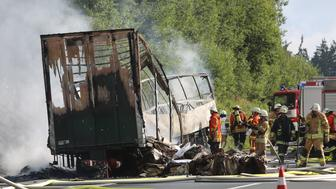MUNCHBERG, BAYERN - JULY 03:  (GERMANY OUT) Firefighters stand at the burned-out wreckage of a passenger bus on the A9 highway in northern Bavaria on July 3, 2017 near Munchberg, Germany. Police have stated that the bus, which was carrying senior citizens from Saxony, crashed into a trailer truck and burst into flames. Police fear 18 people are dead and 30 injured in what is among Germany's worst bus accidents.  (Photo by Stringer/Getty Images)
