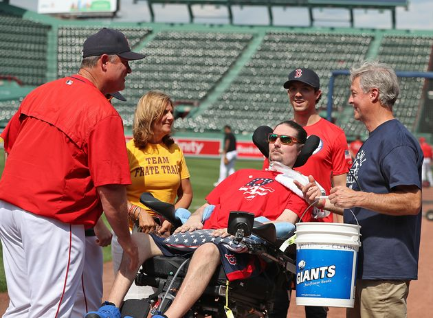 Boston Red Sox manager John Farrell greets Frates and his family at Fenway Park in Boston in June. During...