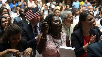 Immigrants smile after receiving their certificates of citizenship at a U.S. Citizenship and Immigration Services Naturalization ceremony in the New York Public Library in New York, U.S., June 30, 2017.  REUTERS/Shannon Stapleton