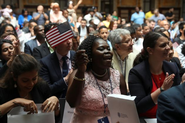 Immigrants smile after receiving their certificates of citizenship at a naturalization ceremony in the...
