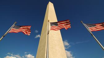 Three American flags fly in the breeze at the Washington Monument in Washington, D.C., United States. International symbol of liberty, freedom, and democracy.