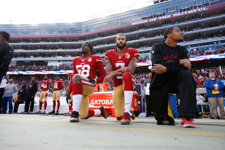 Kaepernick, center, kneels during the national anthem on Jan. 1, 2017. His teammates Eli Harold, left, and Eric Reid, right,