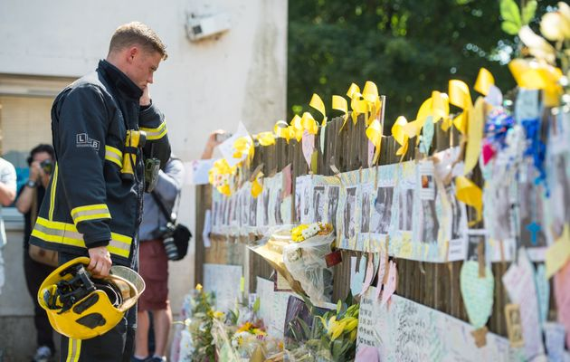 A firefighter views tributes at Latymer Community