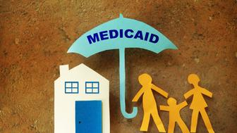 Paper cutout family with house under a Medicaid umbrella