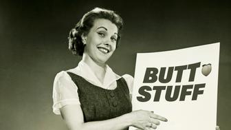 Woman holding blank sheet of paper, posing in studio, (B&W), portrait