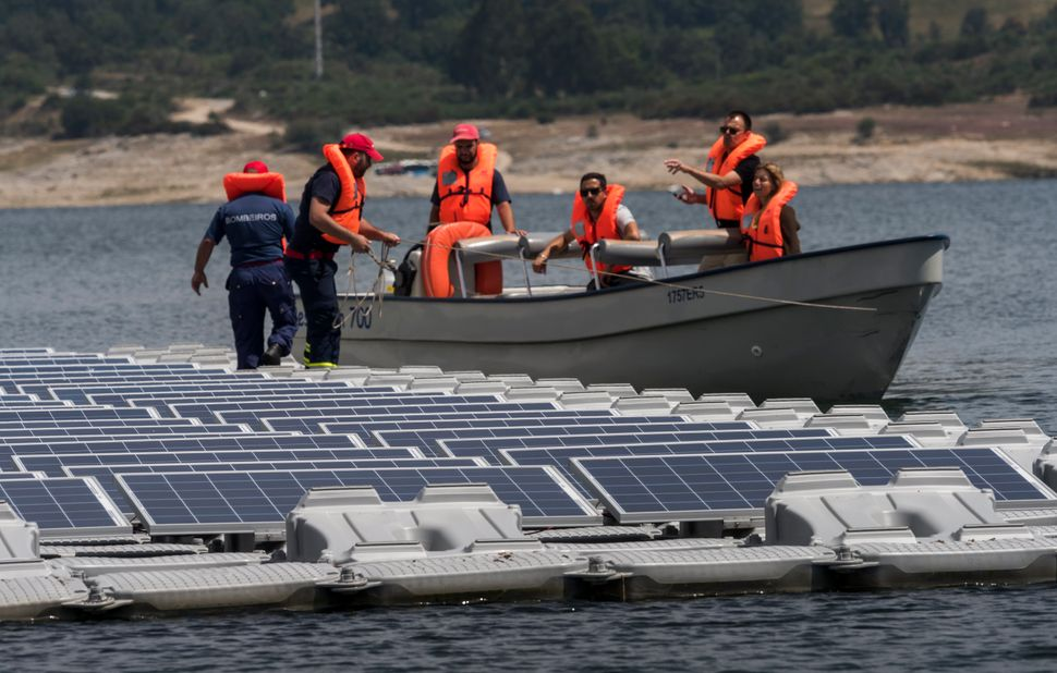 Workers access the panels by boat.
