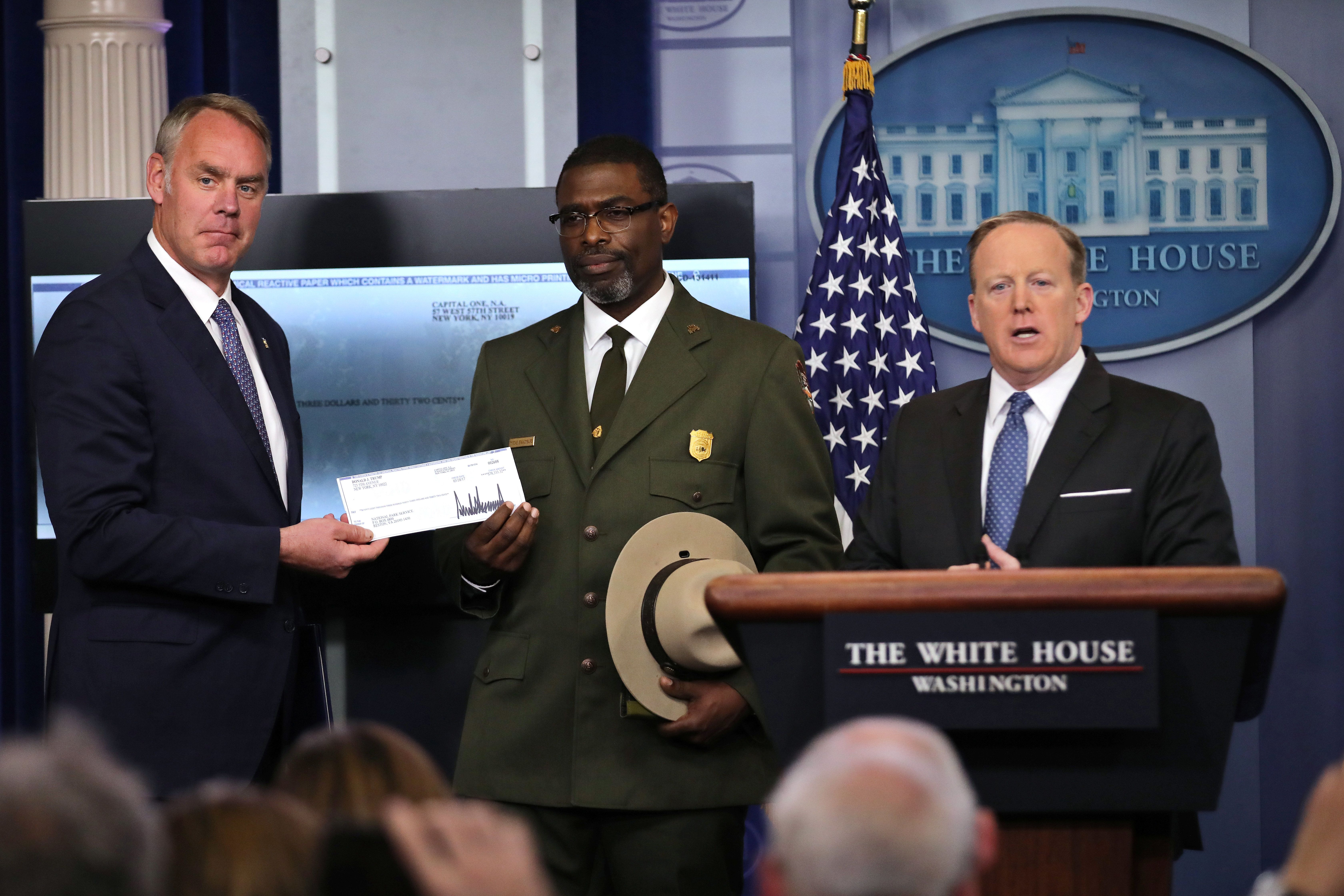 Secretary of the Interior Ryan Zinke seen holding a check announcing President Donald Trump's intended donation to the N