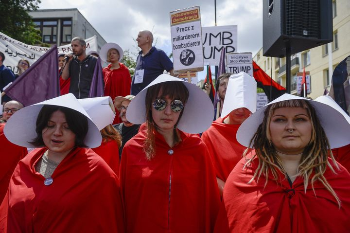 Four handmaids protest Trump's visit to Poland.