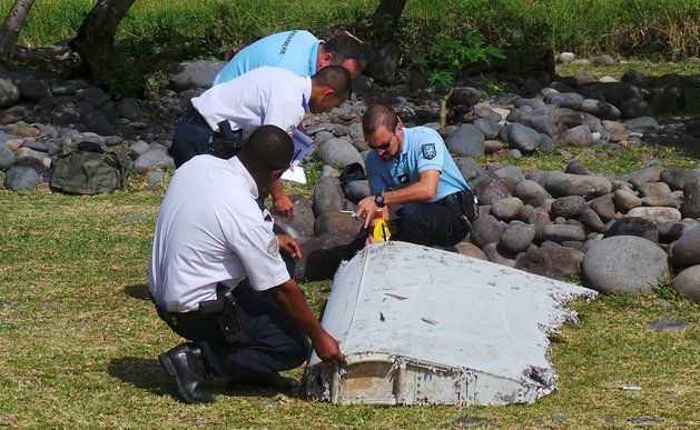 French gendarmes and police inspecting a large piece of plane debris which was found on the beach on...
